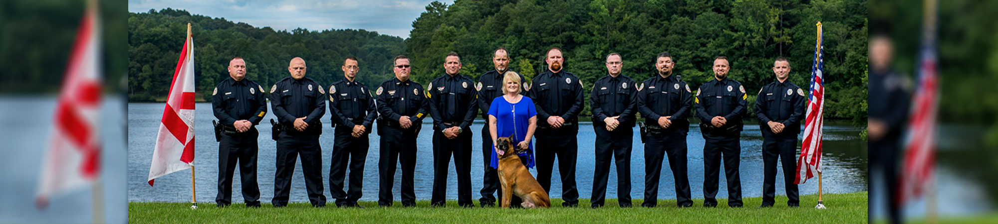 police officers and police dog lined up in front of lake